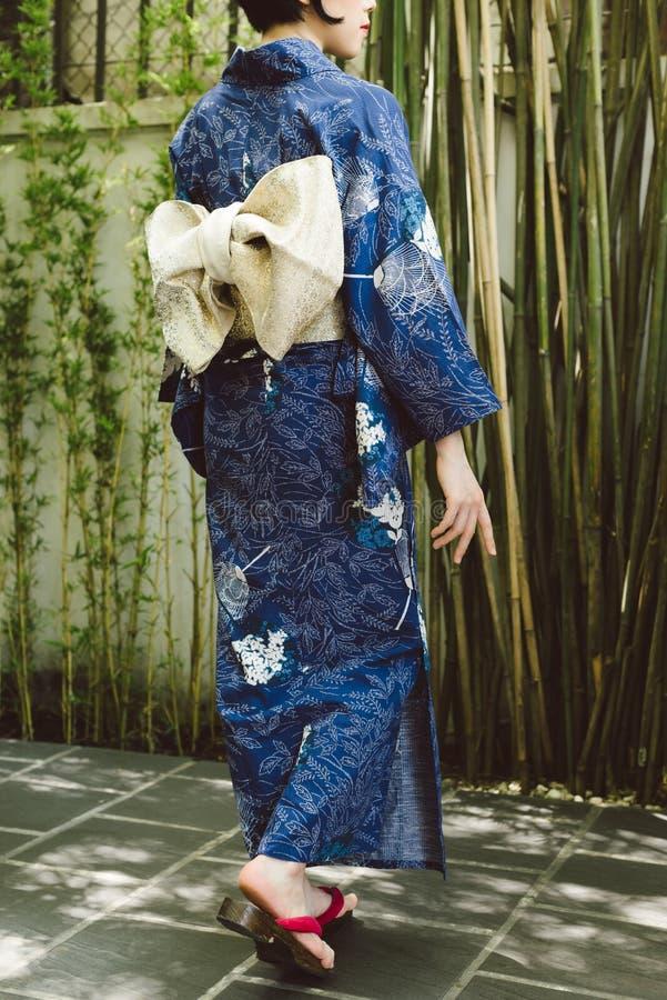 Mujer en kimono y zapatos del geta imagenes de archivo