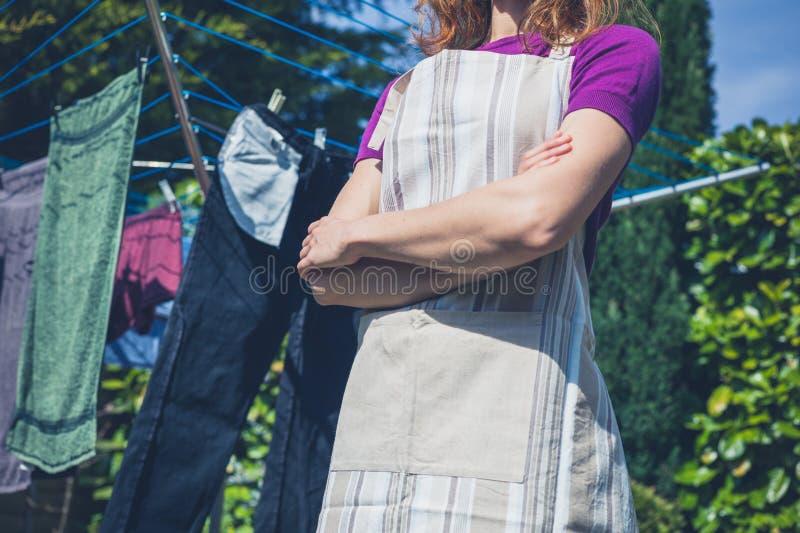 Mujer en línea de ropa del delantal que hace una pausa foto de archivo libre de regalías