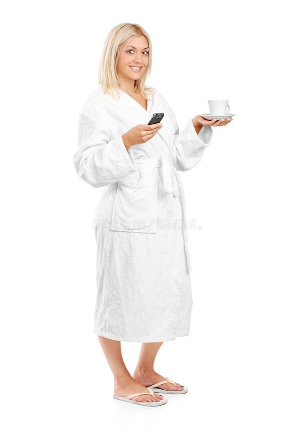 Mujer en la albornoz que sostiene una taza y un teléfono de café imagenes de archivo