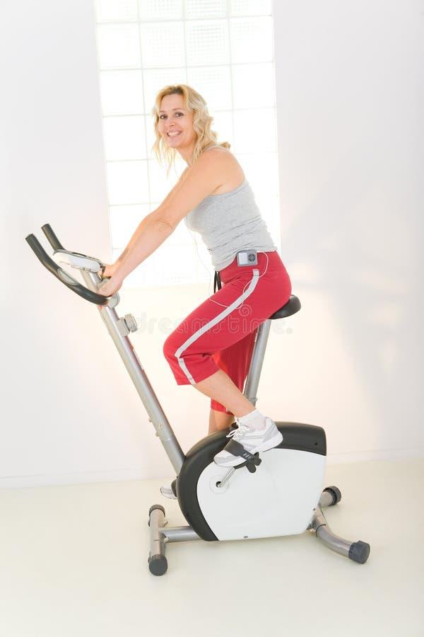 Mujer en la bici de ejercicio fotos de archivo