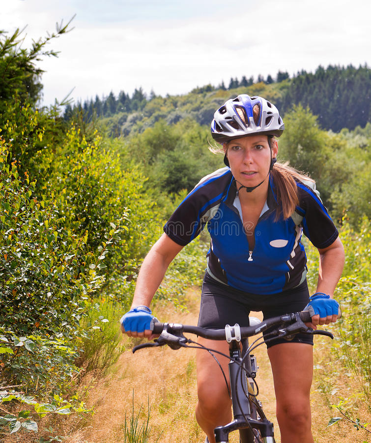Mujer en la bici de montaña imagen de archivo libre de regalías