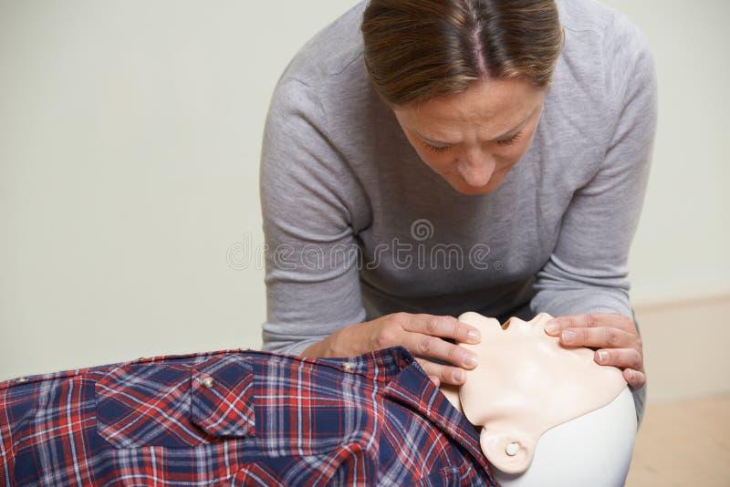Mujer en la boca de ejecución de la clase de los primeros auxilios para articular la resucitación imagen de archivo libre de regalías