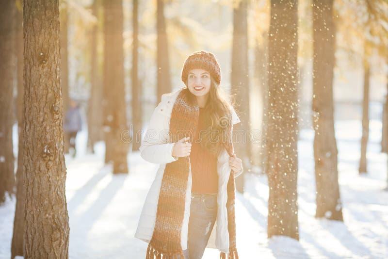 Mujer en la bufanda y el sombrero que se divierten en bosque del invierno fotos de archivo libres de regalías