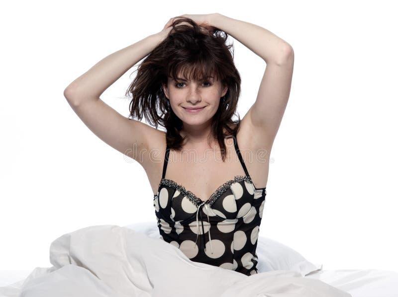 Mujer en la cama que despierta imagenes de archivo