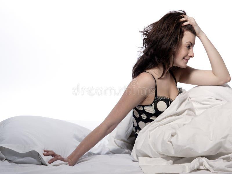 Mujer en la cama que despierta foto de archivo