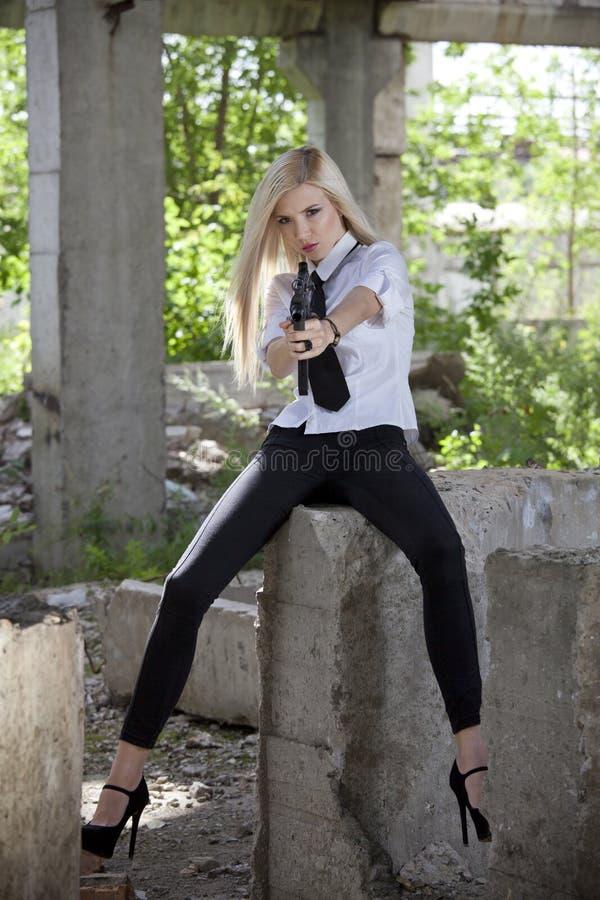 Mujer en la camisa blanca y lazo que sostiene el arma imagenes de archivo