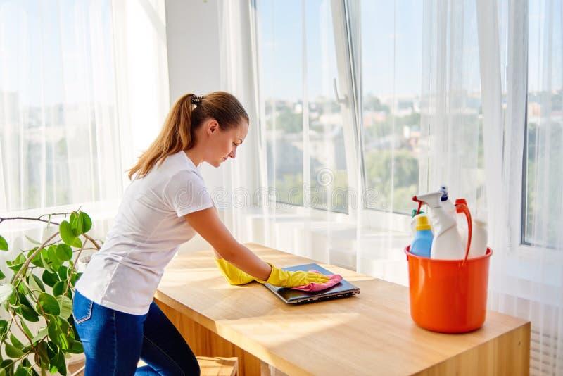Mujer en la camisa blanca y los guantes de goma protectores amarillos que limpian en casa y que limpian el polvo con el trapo ros imagen de archivo