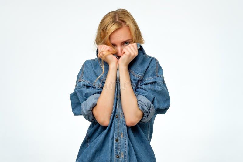 Mujer en la camisa r de los vaqueros del dril de algodón que oculta su cara Ella quiere permanecer el an?nimo foto de archivo libre de regalías
