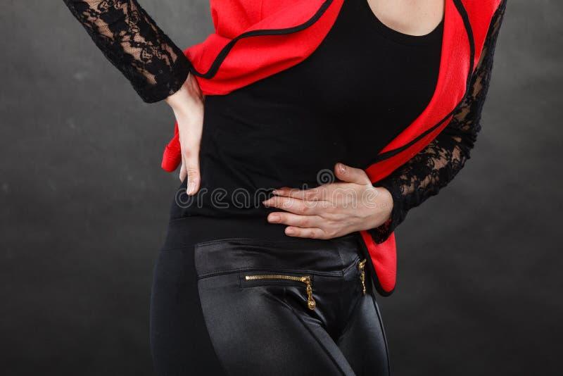 Mujer en la camisa roja que tiene dolor de estómago fotografía de archivo