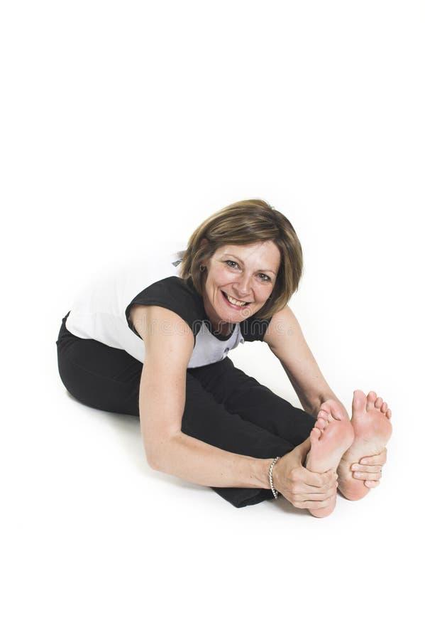 Mujer en la camiseta blanca que hace yoga fotografía de archivo