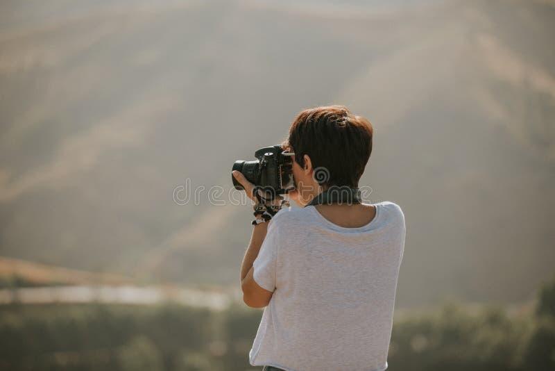 Mujer en la camiseta que toma una foto con una cámara del dslr en naturaleza con luz del día fotos de archivo