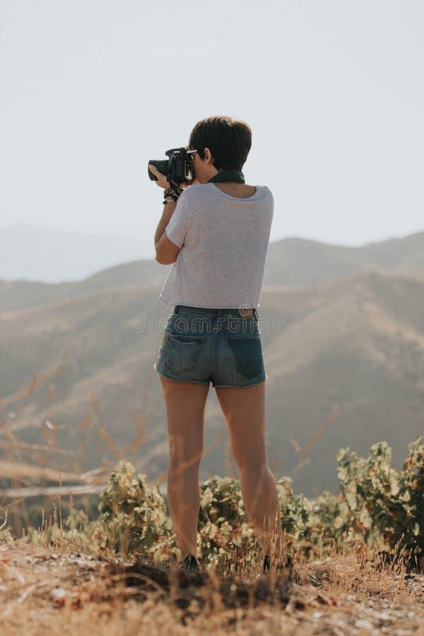 Mujer en la camiseta que toma una foto con una cámara del dslr en naturaleza con luz del día foto de archivo libre de regalías