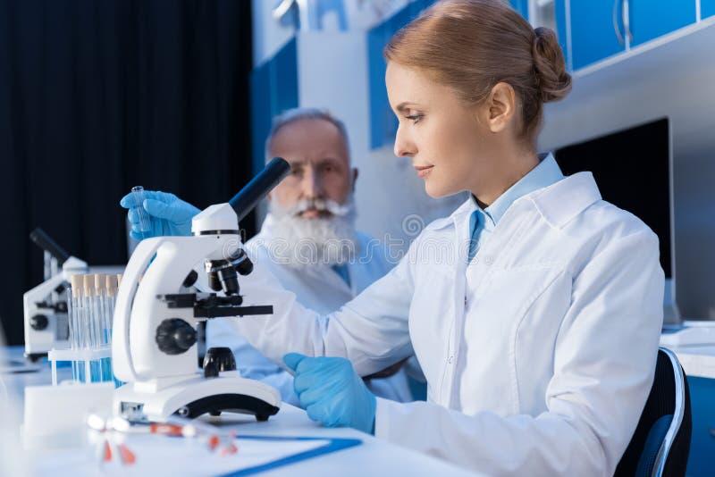 Mujer en la capa del laboratorio que trabaja con el microscopio en el laboratorio científico imágenes de archivo libres de regalías