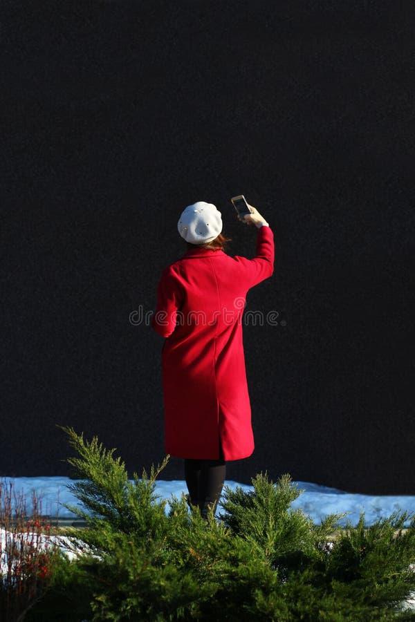 Mujer en la capa roja que hace el selfie en un día soleado Visión posterior foto de archivo
