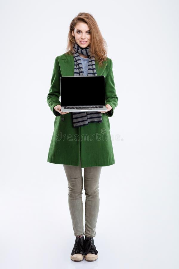 Mujer en la capa verde que muestra la pantalla de ordenador portátil en blanco imagenes de archivo