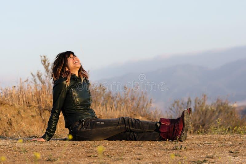 Mujer en la chaqueta de cuero asentada en la risa de tierra fotografía de archivo libre de regalías