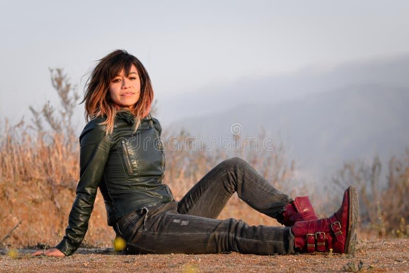Mujer en la chaqueta de cuero verde asentada en la tierra fotos de archivo libres de regalías