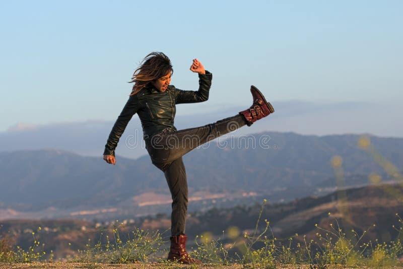 Mujer en la chaqueta de cuero y botas que golpean el aire con el pie imagen de archivo libre de regalías