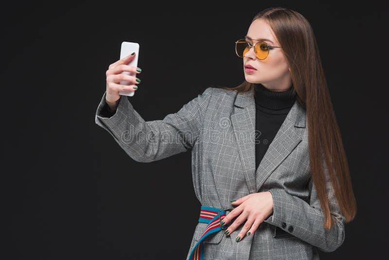 Mujer en la chaqueta gris que toma el selfie con smartphone fotografía de archivo libre de regalías