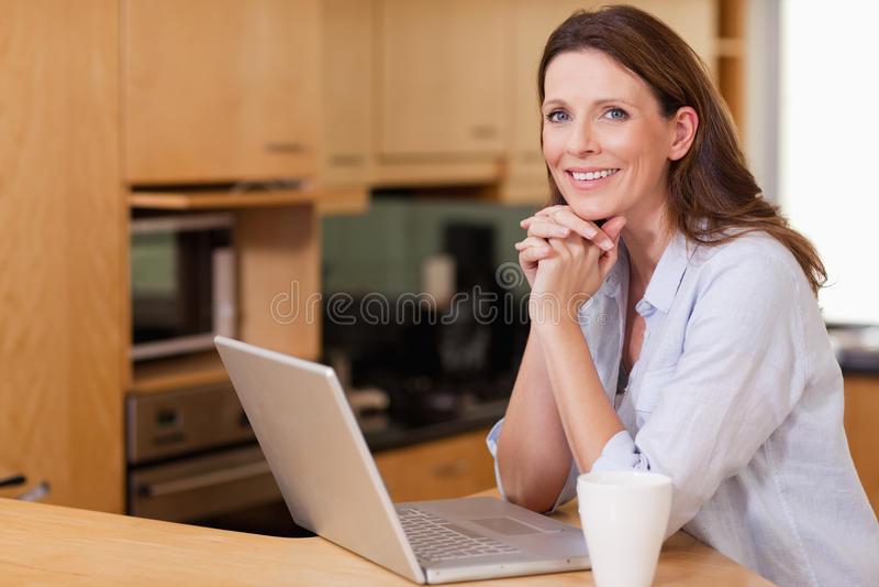 Mujer en la cocina con su computadora portátil fotos de archivo