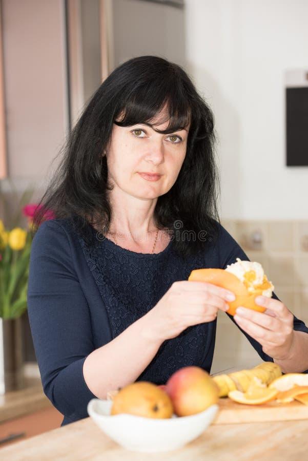 Mujer en la cocina con una naranja fotografía de archivo