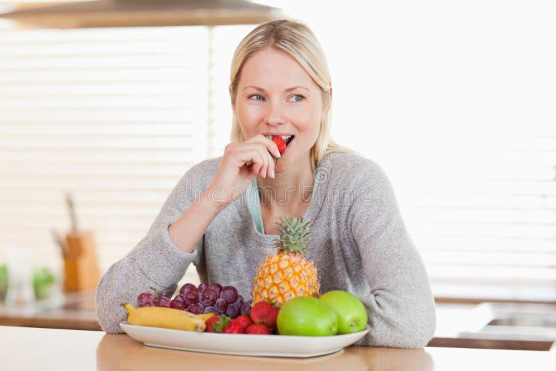 Mujer en la cocina que mordisca algunas frutas foto de archivo