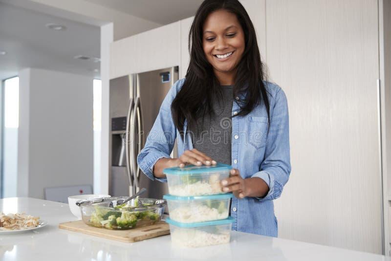 Mujer en la cocina que prepara la comida de alto valor proteico y que pone porciones en los envases de pl?stico foto de archivo
