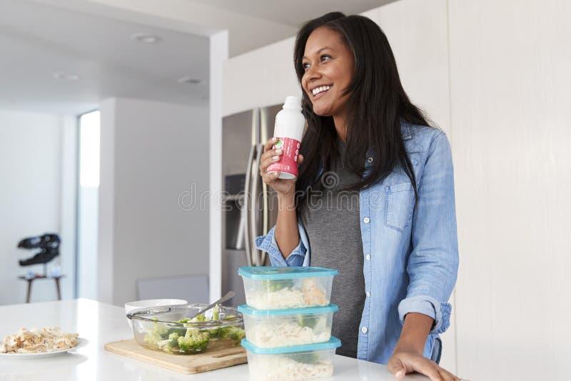 Mujer en la cocina que prepara sacudida de consumición de la proteína de la comida sana de la botella imagenes de archivo