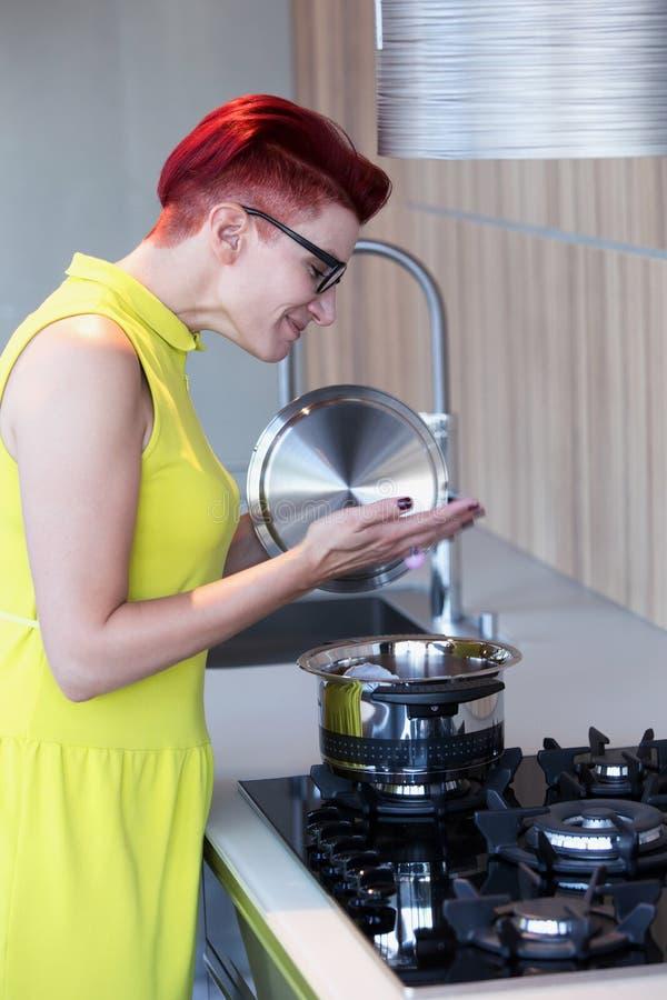 Mujer en la cocina que se coloca en la estufa imagen de archivo