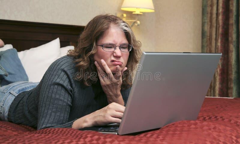 Mujer en la computadora portátil en cama fotos de archivo