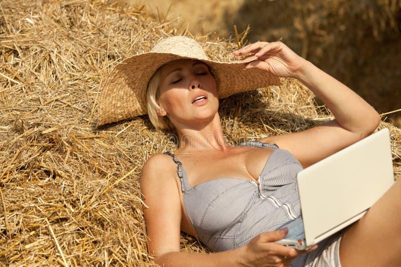 Mujer en la computadora portátil en pila del heno imágenes de archivo libres de regalías