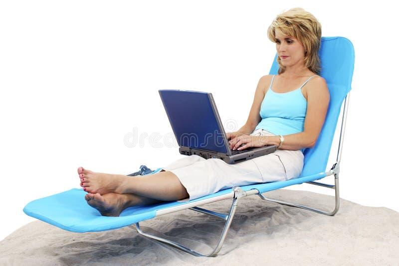 Mujer en la computadora portátil en silla de salón imagenes de archivo