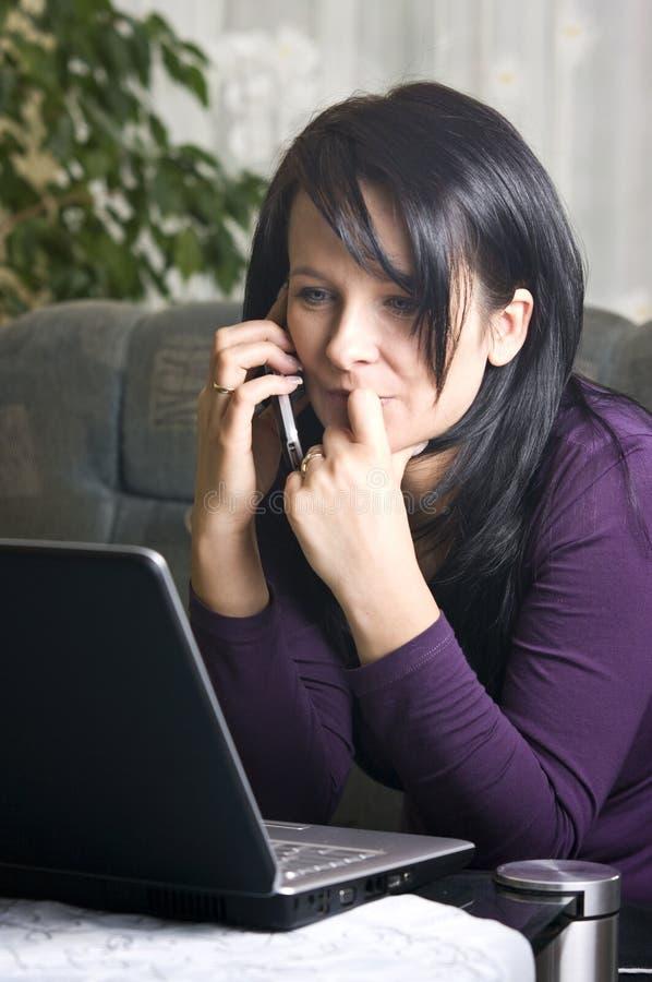 Mujer en la computadora portátil y el teléfono foto de archivo libre de regalías