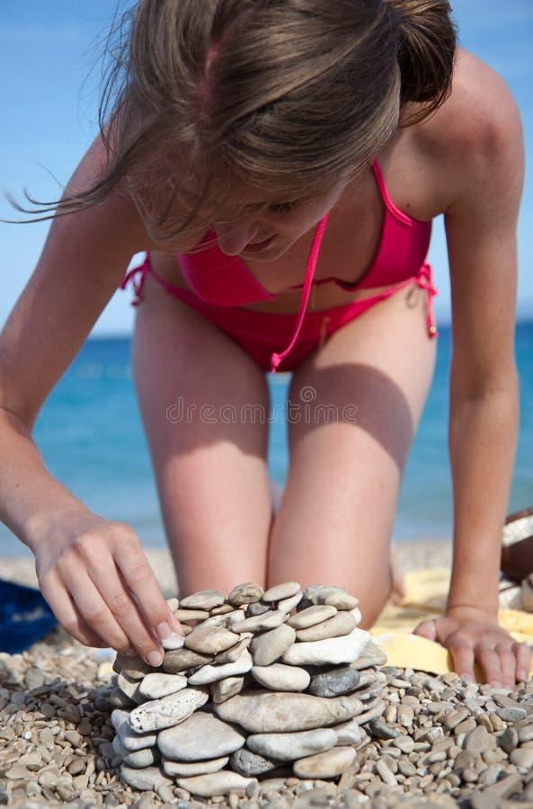 Mujer en la construcción de edificios de la playa de guijarros fotos de archivo