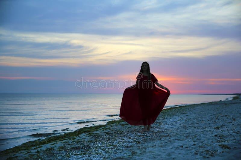 Mujer en la costa de mar en puesta del sol imagenes de archivo