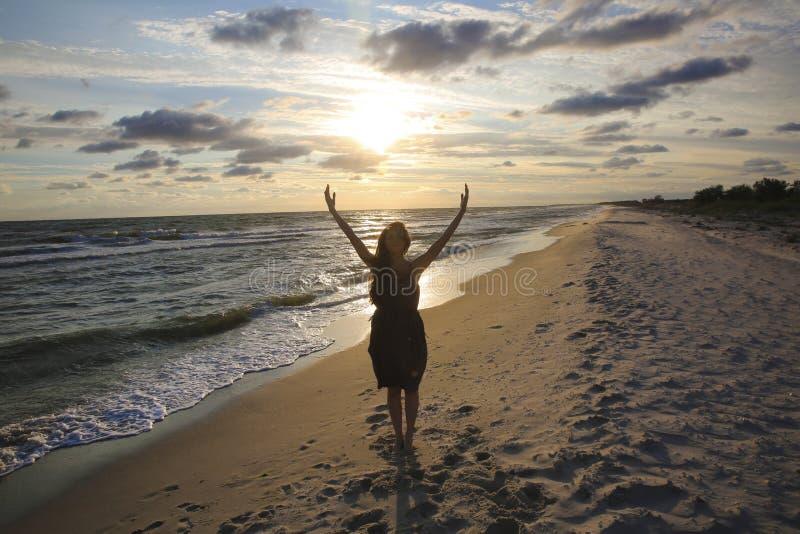 Mujer en la costa de mar en puesta del sol imágenes de archivo libres de regalías