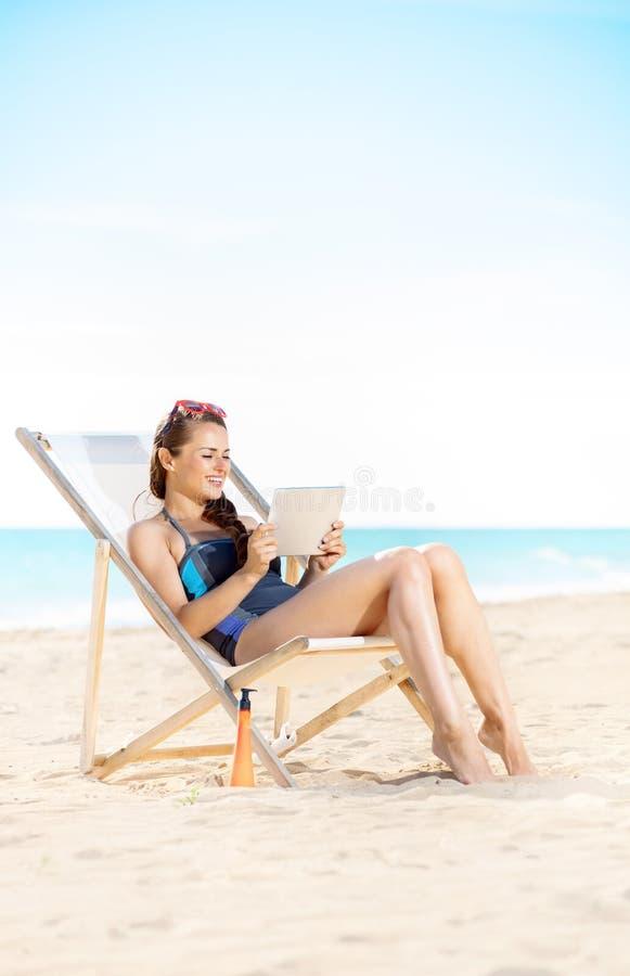 Mujer en la costa usando la tableta mientras que se sienta en silla de playa imagenes de archivo