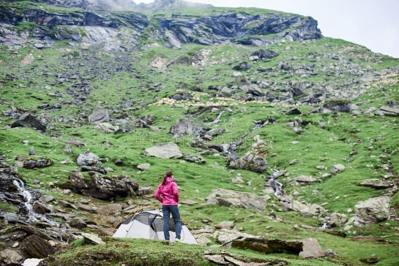 Mujer en la cuesta rocosa de las montañas de Fagaras que goza de las colinas de la visión imagen de archivo