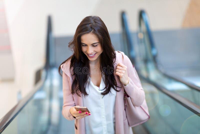 Mujer en la escalera móvil fotografía de archivo