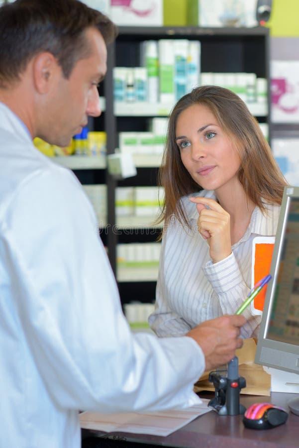 Mujer en la farmacia imagenes de archivo