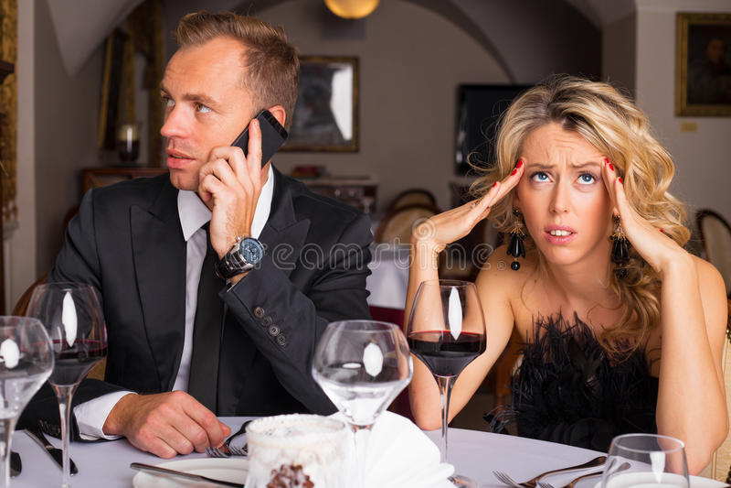 Mujer en la fecha de la cena que es molestada del hombre que habla en el teléfono fotografía de archivo