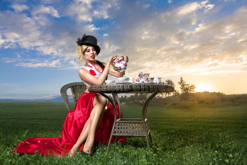 Mujer en la fiesta del té del país de las maravillas fotos de archivo