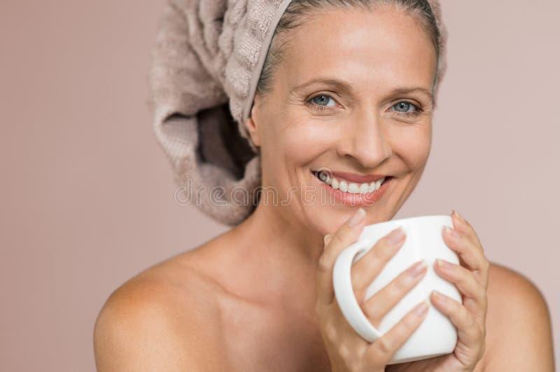 Mujer en la infusión de consumición de la toalla fotografía de archivo libre de regalías