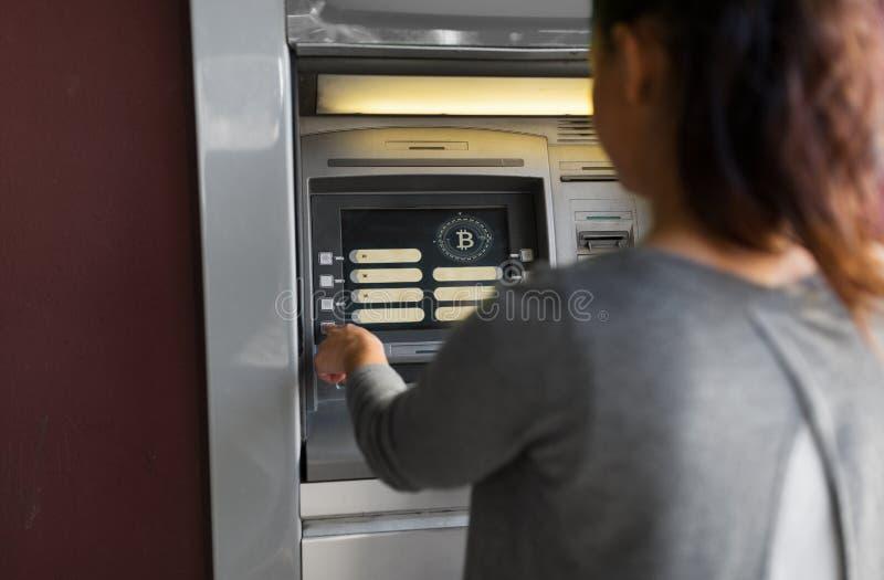 Mujer en la máquina de la atmósfera con el icono del bitcoin en la pantalla fotografía de archivo