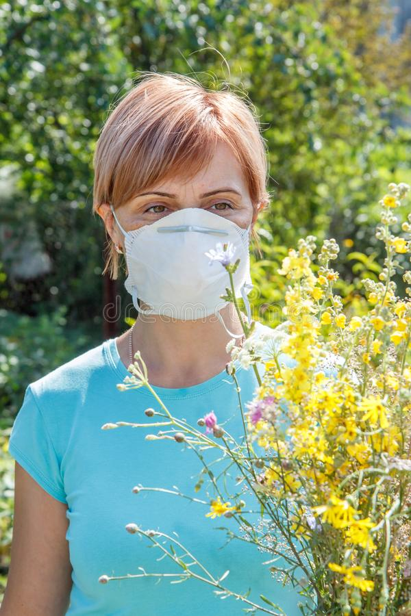 Mujer en la máscara de la protección que sostiene el ramo de wildflowers y de tryi foto de archivo libre de regalías