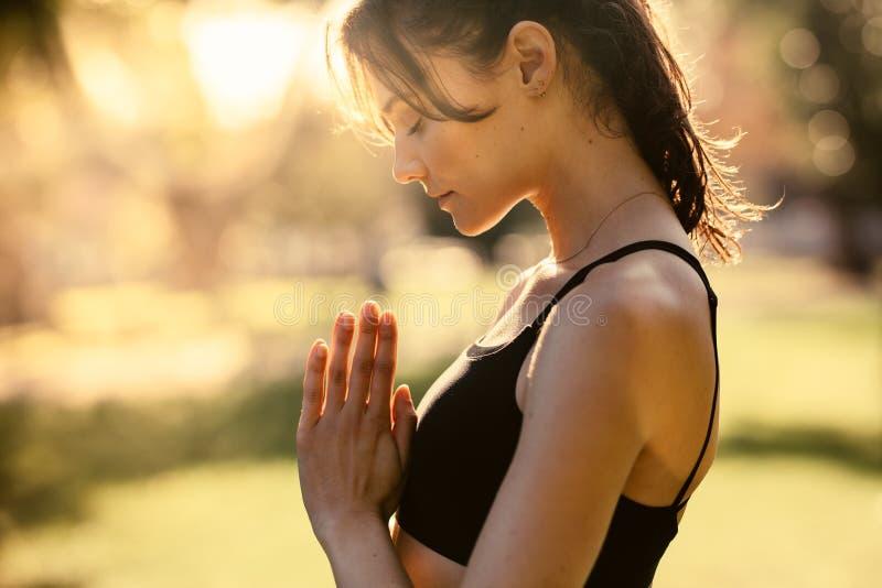 Mujer en la meditación practicante del parque foto de archivo