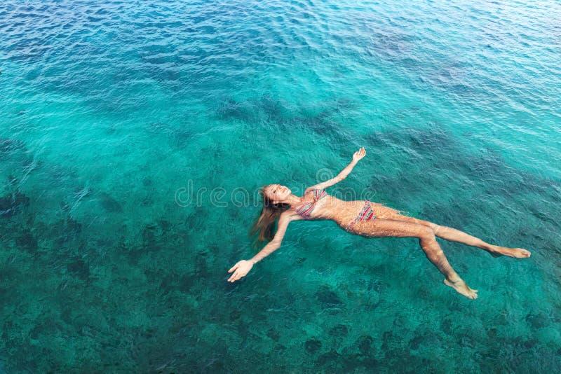 Mujer en la mentira de relajación del bikini en el agua fotografía de archivo