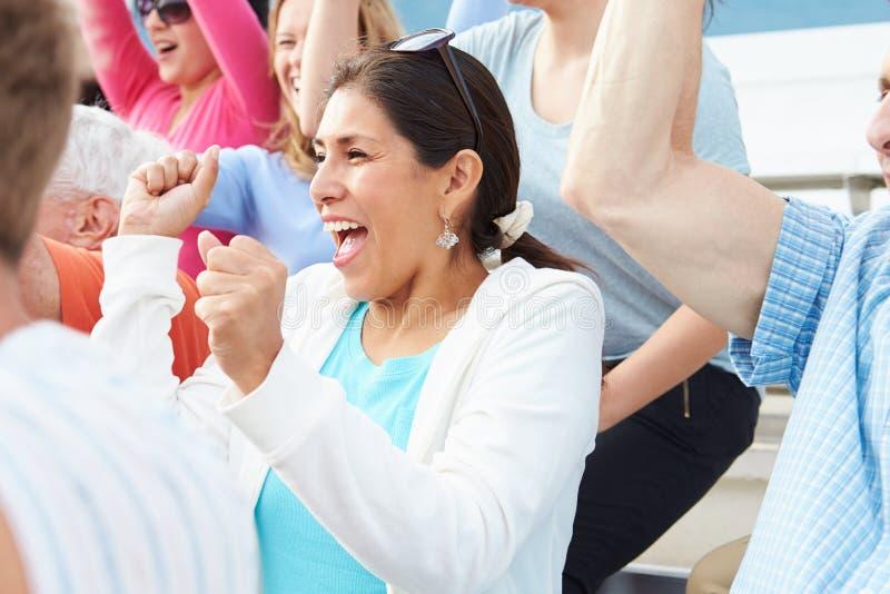 Mujer en la muchedumbre que celebra en el acontecimiento deportivo fotografía de archivo