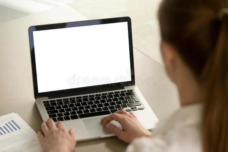 Mujer en la oficina que trabaja en el ordenador portátil con la pantalla en blanco de la maqueta imágenes de archivo libres de regalías
