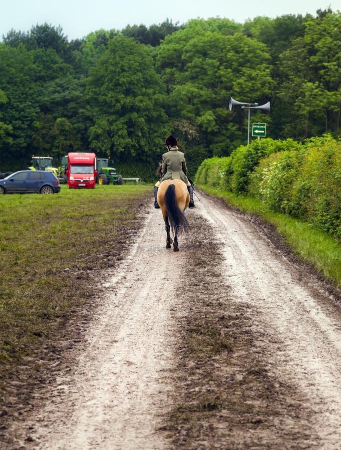 Mujer en la parte posterior del caballo que monta abajo de carril del país foto de archivo